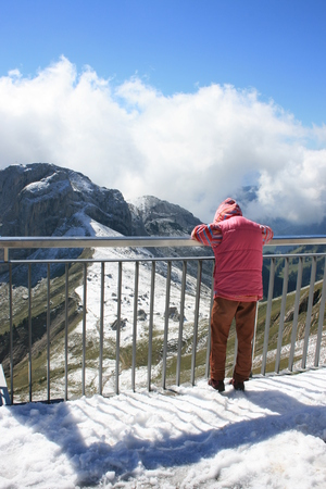 Child looking out at the Swiss Alps from the top of Mount Pilatus.