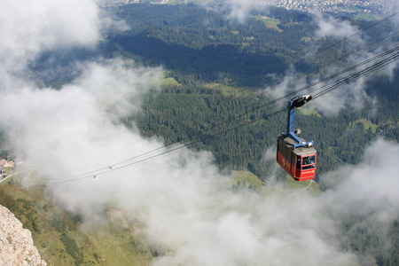 Gondola on the way to a mountain summit. Imagens