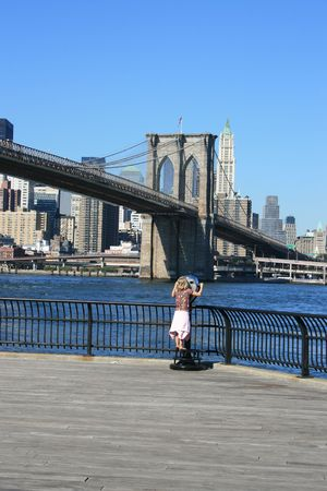 operated: A young girl looking at downtown Manhattan and the Brooklyn Bridge through a coin operated view finder.
