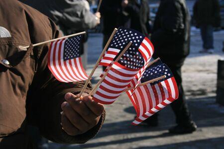 american flags: Hombre sosteniendo banderas norteamericanas de miniatura.
