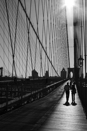 People walking along the path of the Brooklyn Bridge.