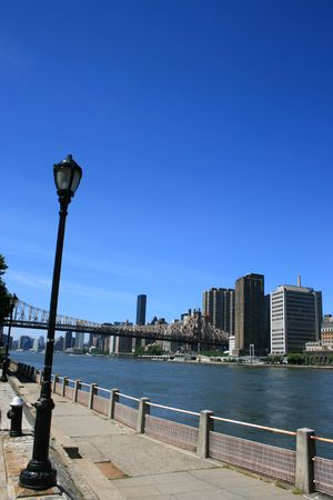 manhattans: Walkway along Manhattans Roosevelt Island. Queensboro Bridge in the background.