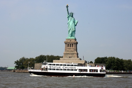 New York City, USA - September 3, 2011 - A cruise ship passing in font of the Statue of Liberty.