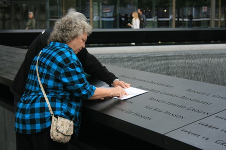 etch: New York City, USA - September 17, 2011 - A couple etch names onto paper at the 911 Memorial at Ground Zero.