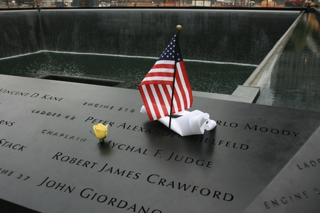 New York City, USA - September 17, 2011 - Flower and flag left at the National 911 Memorial at Ground Zero.
