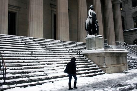 federal hall: New York City, USA - February 9, 2013: Woman walks through Lower Manhattan following Winter Storm Nemo.