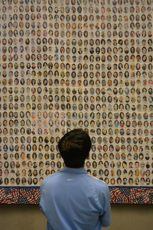 New York City, USA - May 17, 2014 - Man looking at photos of victims of the attacks on the Twin Towers at the National 9 11 Memorial Museum at Ground Zero