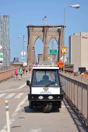 patrolling: New York City, USA - August 10, 2014 - NYPD patrolling the walkway along the Brooklyn Bridge