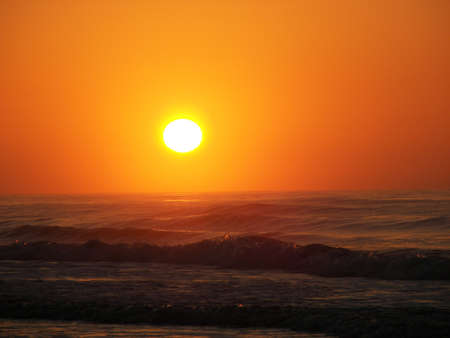 A sunrise over the ocean with colors of orange,red and yellow in a beautiful sky photo