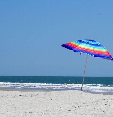A multi-colored beach umbrella on a deserted beach