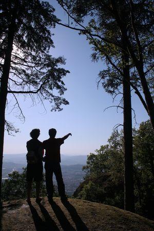 serenety: Couple watching the horizon.Man pointing. Stock Photo