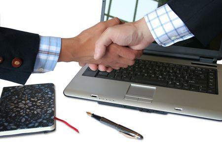Hand shake near a laptop