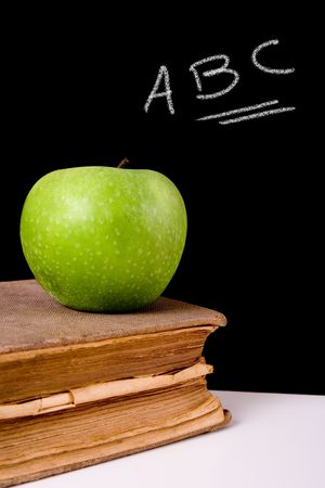 Green apple on top of a very old book. Chalkboard with �ABC� letters on it as background