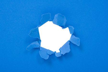 penetracion: Gran agujero en una hoja de papel azul  Foto de archivo