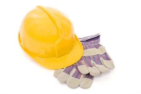 Yellow safety helmet and a pair of industrial protective gloves over white background Stock Photo - 831316