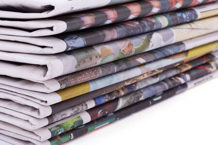 educative: Pile of newspapers to recycle over white background. Shallow depth of field.