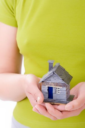 Woman holding a rustic miniature house in his hand. Shallow depth of field.