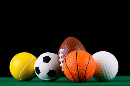 eclecticism: Miniaturized sport balls over black background. Shallow depth of field. Focus is on the front. Stock Photo