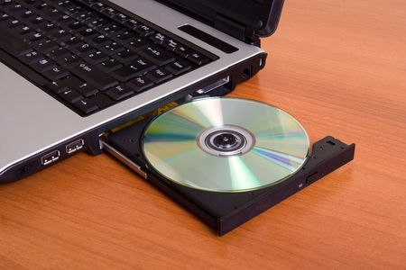 Partial view of a laptop with the dvd recorder opened on a wood table Stock Photo - 1214609
