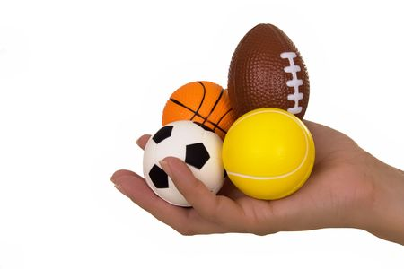 eclecticism: Feminine hand holding miniaturized rubber sport balls over white background