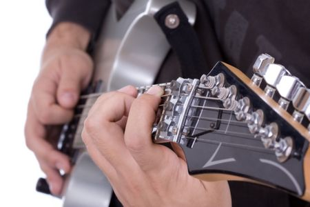 Electric guitar close up showing fingers playing it over white background