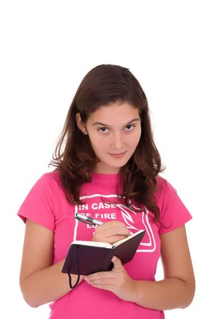 Beautiful young girl writing on her notebook photo