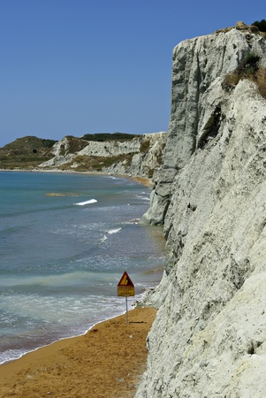 Sandy beach and dangerous cliffs at sunny summer day.