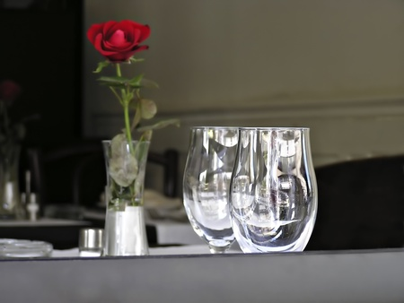 Blurred red rose in vase and two empty wine glasses focused in foreground.