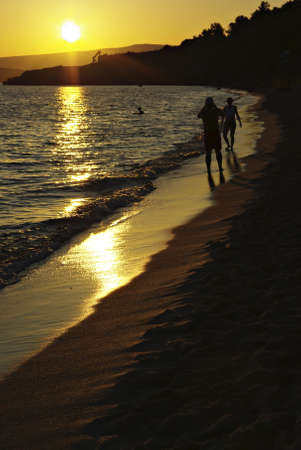 Sunset at sandy beach, couple of people walking together. Stock Photo