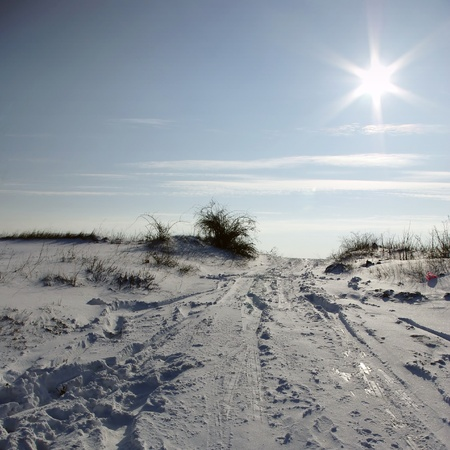Snowy winter landscape with clear blue sky and sun.