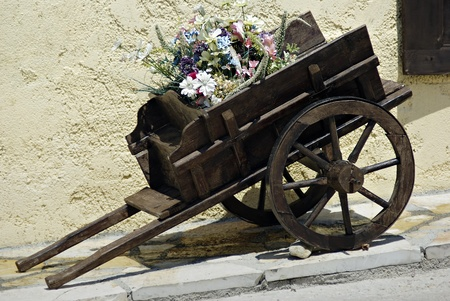 Old small wooden coach full of summer flowers at sunny day.