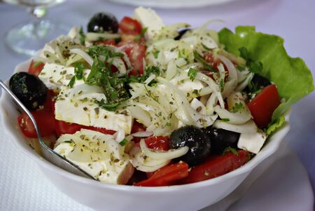 Traditional greek salad consists of tomato, feta cheese, onion, green paprika, cucumber, olives and garlic in white plate with fork. Stock Photo