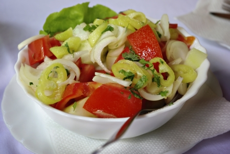 Traditional mixed salad consists of tomato, onion, green pepper, cucumber and spices in white plate with fork  photo