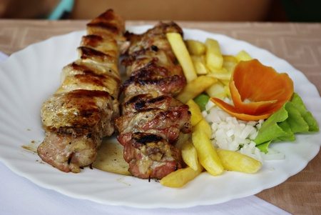 Traditional greek grill with vegetables served on white plate. photo