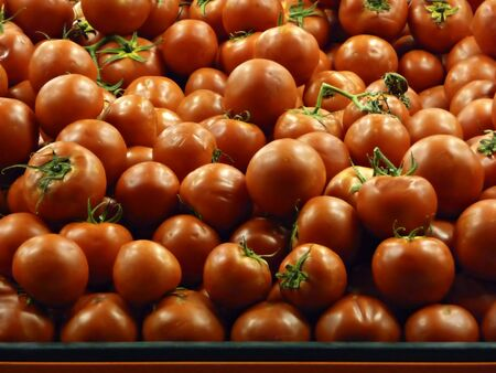 Stand with lot of tomato at grocery shop.