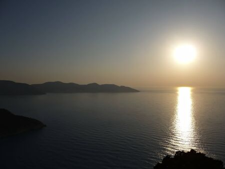 Sunset at one of greece islands, skyline with local hills and sun reflection in sea water.