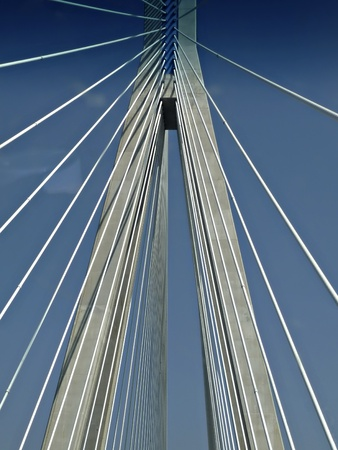 Suspension cables at modern highway bridge against clear blue sky at sunny summer day