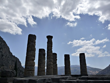 Ruins of Apollo temple at Delphy at sunny summer day agains cloudy sky. Stock Photo
