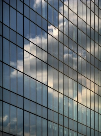 Modern glas  building against clear blue sky with sun reflection in windows  Stock Photo