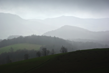 Foggy and rainy mountain landscape, dull and cloudy sky in background  Stock Photo