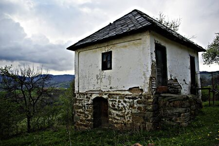 Abandoned old mountain cabin and leafless tree against stormy cloudy sky Stock Photo - 16999928