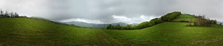 Panoramic shot of misty cloudy day at mountain highlands, green meadows and small forest