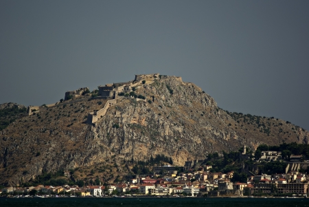Panoramic image of Nafplio with ancient castle at the top of hill in background and clear blue sky at summer sunny day  Stock Photo