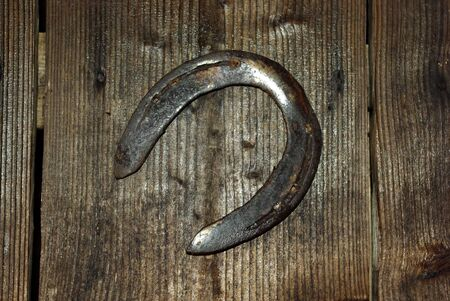 Old rusted horse shou hanging on stable wooden door  photo