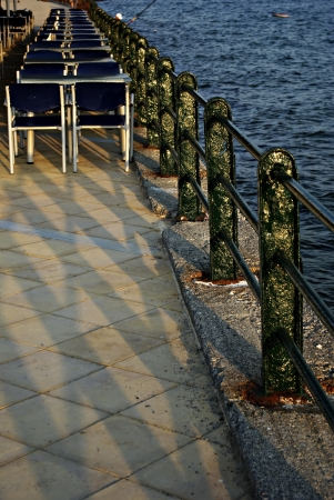 Restaurant and fence on sea shore at sunny summer sunset  photo
