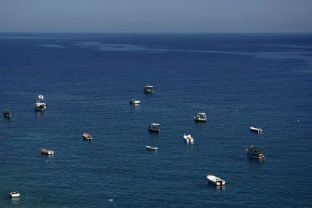 Small fisherman boats and horizon at background against clear blue sky at sunny summer day  photo