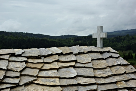The roof of the old church covered with stone slabs and a stormy sky in the background.