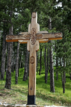 Wooden cross in a pine forest on a sunny summer day.