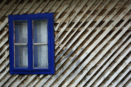 Blue window frame on the old wooden hut. photo