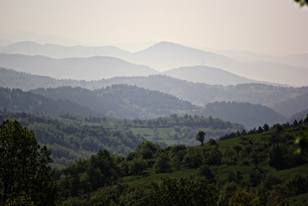 Forested mountain landscape with the peaks that disappear into the mist in the distance. photo